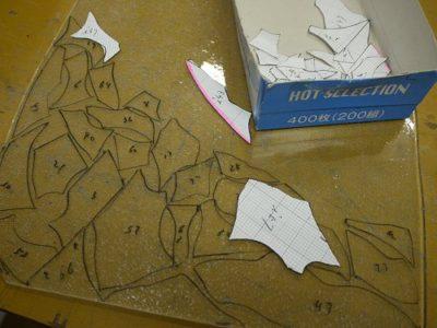 背景にあたるクリアのガラスに、型紙を当てて輪郭を描いています