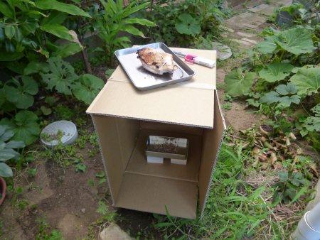 場所は我が家の庭の片隅。鶏肉をダンボールに吊るし、皿にはスモークチップスという燻製の素となる木片を敷きつめ、火をつけます。